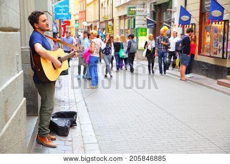 Stockholm, Sweden - July 25, 2017: Unidentified musician plays guiar in central shopping street of Gamla Stan in Stockholm