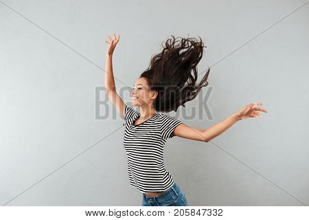 Happy satisfied asian woman with flying hair standing with her arms raised isolated over gray background