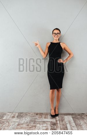 Full length portrait of a cheerful young businesswoman in black dress and eyeglasses standing and pointing finger away at copy space isolated over gray background
