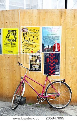 Stockholm, Sweden - July 25, 2017: Bicycle near fence with ad posters in Stockholm