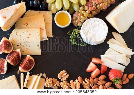 Tasting cheese dish with herbs and fruits on old black wooden table. Food for wine and romantic, cheese delicatessen. Menu design horizontal. Top view.
