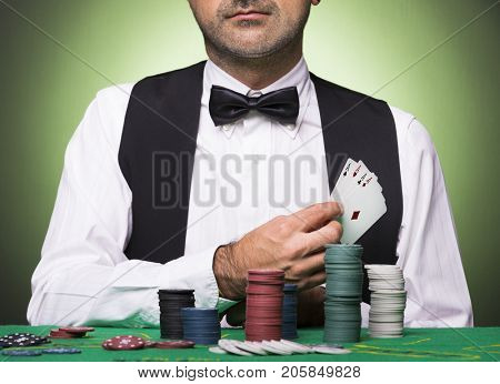 Poker player holding four aces cards at the table
