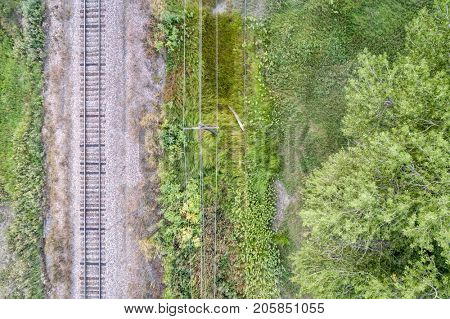 aerial view of single railroad tracks and electric wires in back country