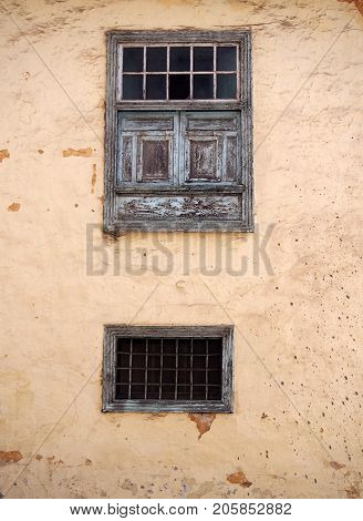 two old wooden windows with ancient faded peeling green paint metal bars shutters and panels on an old plastered peeling concrete terracotta and beige wall with stains and cracks