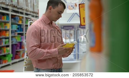 young guy buys liquid soap in a store or supermarket
