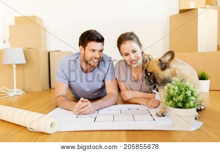 mortgage, people and real estate concept - happy couple with boxes, blueprint and dog moving to new home
