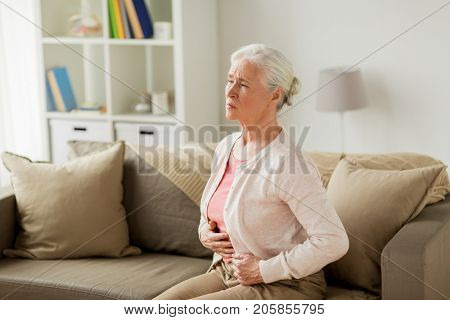 old age, health problem and people concept - senior woman suffering from stomach ache at home