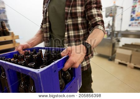 manufacture, business and people concept - man with glass bottles in box at craft brewery or non-alcoholic beer production plant