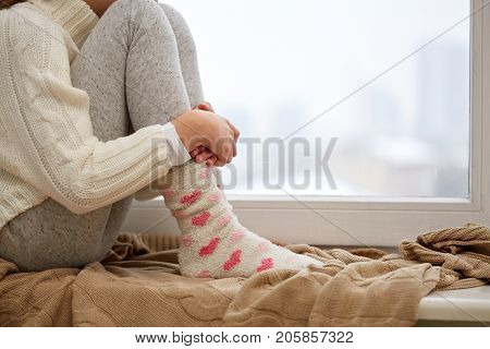 childhood, sadness and people concept - close up of girl in sweater sitting on sill at home window in winter poster