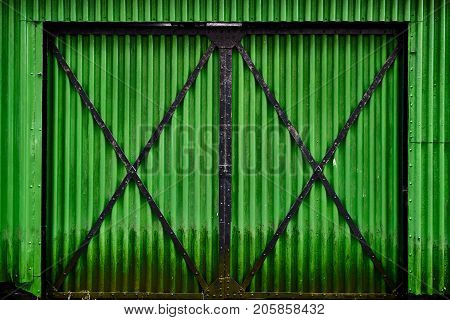 Old green corrugated iron gate of a barn in Norway with black beams