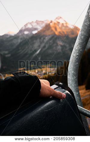 point of view from the chair lift over the valley and mountains with an arm the foreground during sunset in Austria