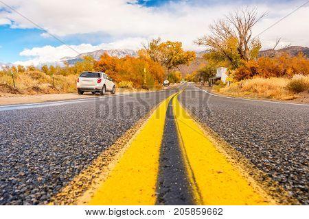 Car on highway shoulder at autumn. California, USA.