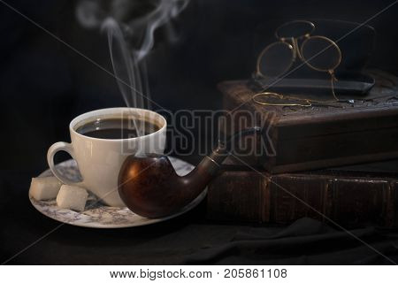 The composition is beautiful from an old book, a cup of coffee, a snuffbox and a pipe to hold a nice evening with an olive box with tobacco