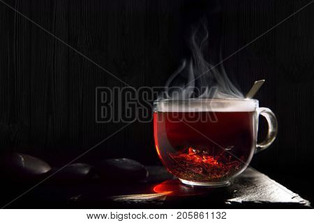 A beautiful, hot, black tea from India on a black flone made of stone. Useful, very strong and thick drink for vivacity