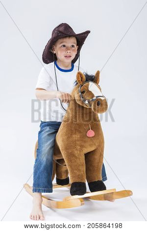 Natural Portrait of Happy Smiling and Glad Caucasian Little Boy in Cowboy Clothing With Symbolic Plush Horse Against White. Horizontal Image Composition