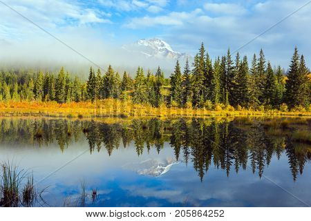 Indian summer in Jasper. Patricia Lake among the firs and pines. The water reflects the snowy peak of the Pyramid Mountain. The concept of extreme and ecotourism