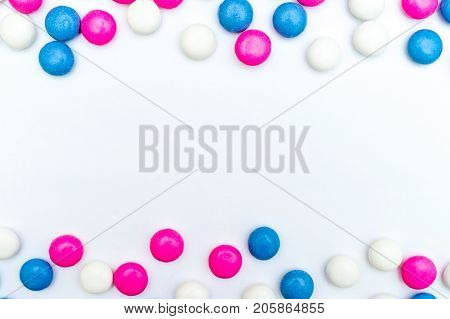 Top view of frame made of colored chocolate coated candy on white background. Copy space