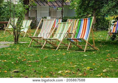 Deckchairs for relaxation. Autumn time. Striped chaise lounges on the grass.