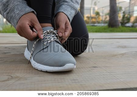Low section of female athlete tying shoelace while kneeling on boardwalk