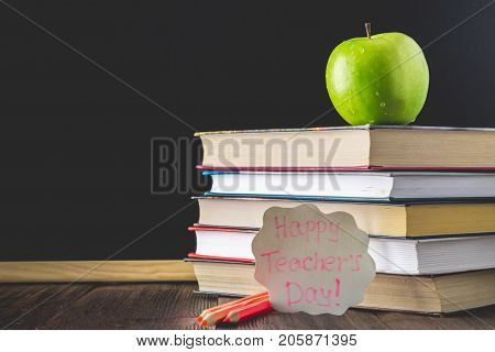 Concept Of Teacher's Day. Objects On A Chalkboard Background. Books, Green Apple, Plaque: Happy Teac