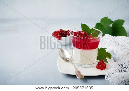 Panna cotta with red currant jelly in vintage glasswith leaves of mint and berries on gray stone or concrete background. Traditional Italian dessert. Selective focus.