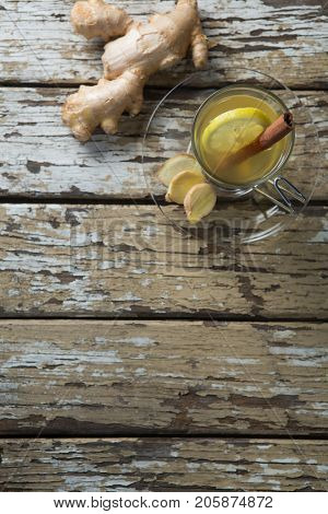 Overhead view of cinnamon and lemon in ginger tea on weathered wooden table