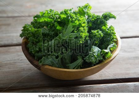 Close-up of kale in bowl on wooden table