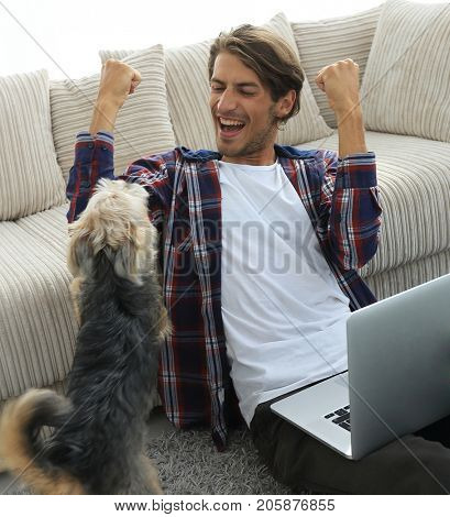 happy guy with laptop jubilant in spacious living room.