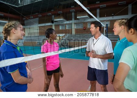 Volleyball coach talking to female players in court