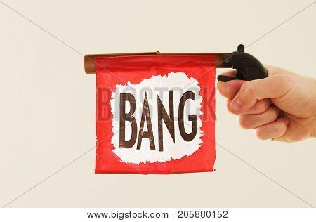 a practice joke gun with a bang sign.