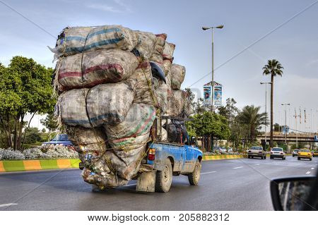 Fars Province Shiraz Iran - 18 april 2017: Overloaded with sacks of household waste the car is moving along the city road.