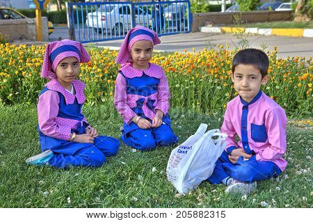 Fars Province Shiraz Iran - 19 april 2017: Three preschool children two girls and one boy dressed in lilac uniform sit on the lawn grass in the city park.