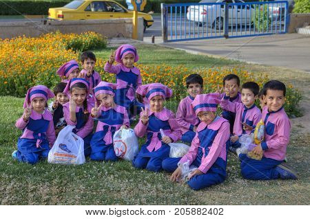 Fars Province Shiraz Iran - 19 april 2017: A group of children boys and girls of pre-school age dressed in pink and blue uniforms posing for photographer sitting on the lawn grass in city park.