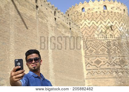 Fars Province Shiraz Iran - 19 april 2017: Young man photographing himself against the background of Karim Khan Citadel tower using iPhone.