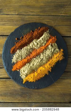 Close-up of various type of spice powder on slate plate