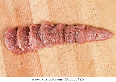 Raw meat pork tenderloin on cutting board ready to cook pork tenderloin cut into pieces of medallions marinated in salt and pepper