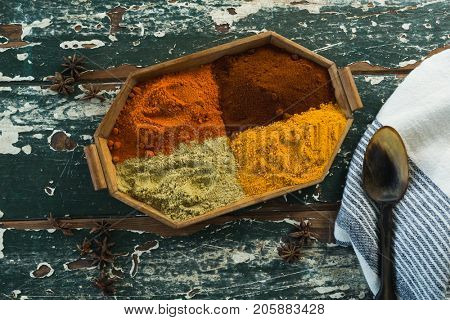 Overhead view of various spice powder in wooden tray