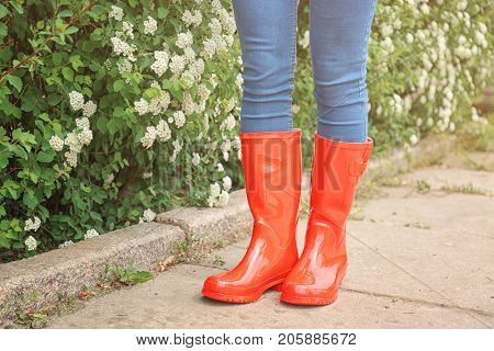 Young woman in red rubber boots outdoors