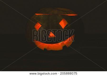 Close up of jack o lantern glowing in darkroom