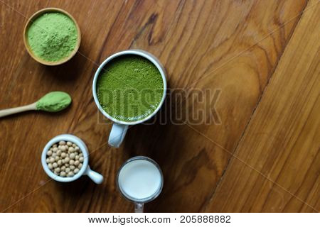 Top View,closes Up Hot Green Tea Matcha Latte On Dark Wooden Tablle. Decorate With Powder Extract An