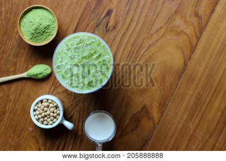 Top View,closes Up Iced Green Tea Matcha Latte On Dark Wooden Tablle. Decorate With Powder Extract A