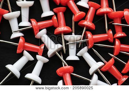 Closeup of group of pushpin thumbtack on black background
