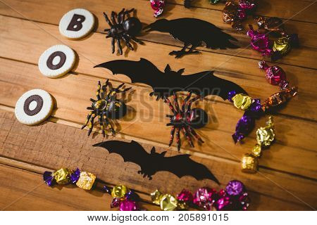 High angle view of cookies with boo text by decorations and chocolates table