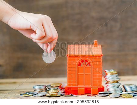 Abstract hand put coins to stack of coins and home on wooden background. Business Finance and time of money home loan concept.