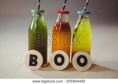 Boo text on cookies by colorful drinks in bottles over white background