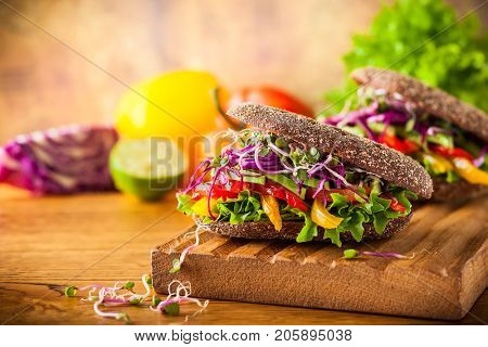 Vegan burger or sandwiches with rye bread, different vegetables and sprouts. Concept of healthy eating or vegetarian food.