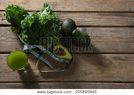 Overhead of mustard greens, avocado, measuring tape and juice on wooden table