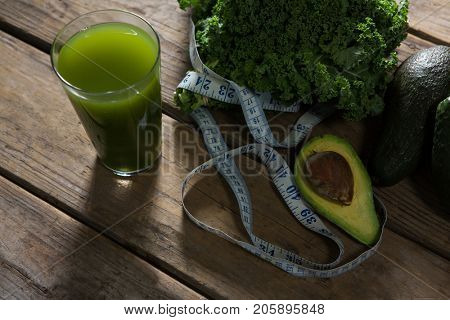 Close-up of mustard greens, avocado, measuring tape and juice on wooden table