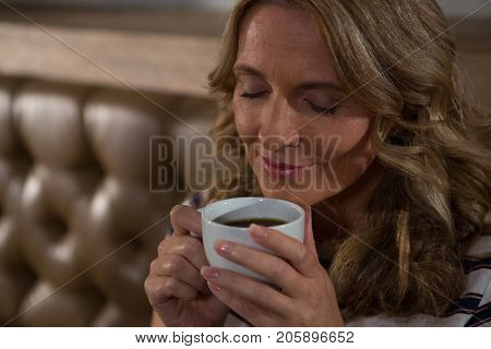 Close-up of happy woman smelling coffee