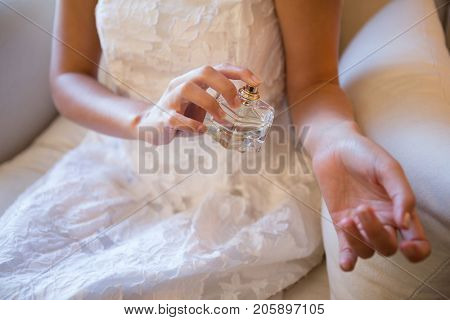 Midsection of bride spraying perfume on hand while sitting at home